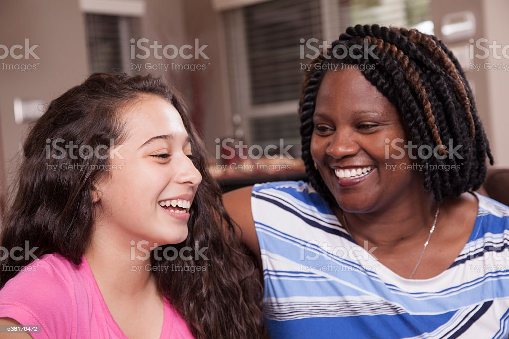 Multi-ethnic family.  Teenage girls and mom at home.  Hugs. stock photo