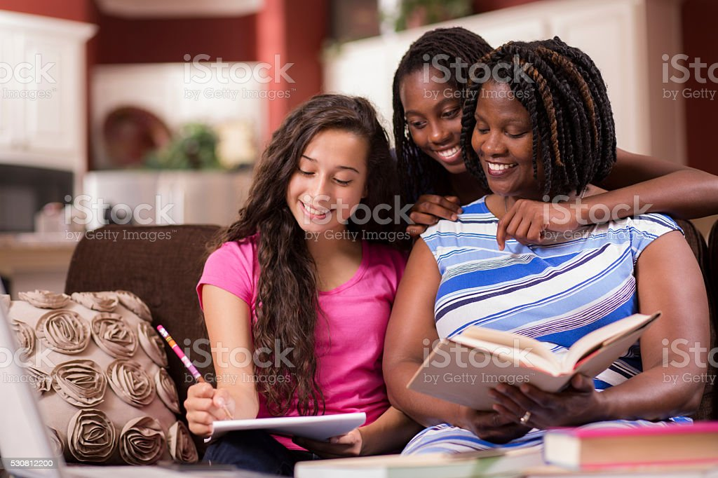 Multi-ethnic family.  Teenage girls and mom at home studying, laughing. stock photo