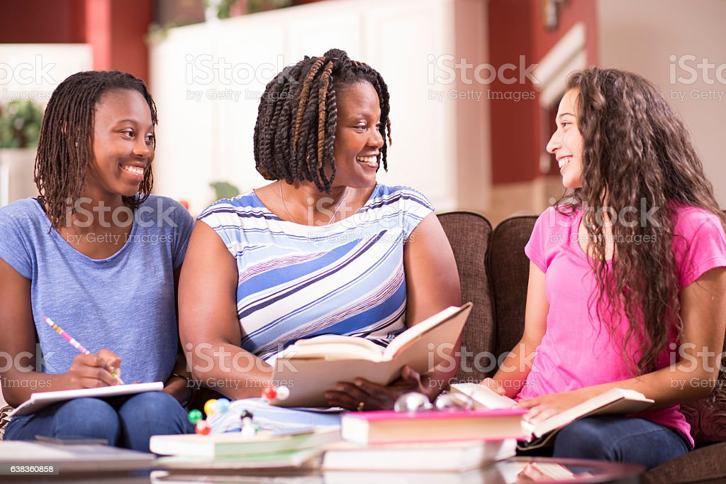 Multi-ethnic family with teenage girls and mom at home studying. stock photo