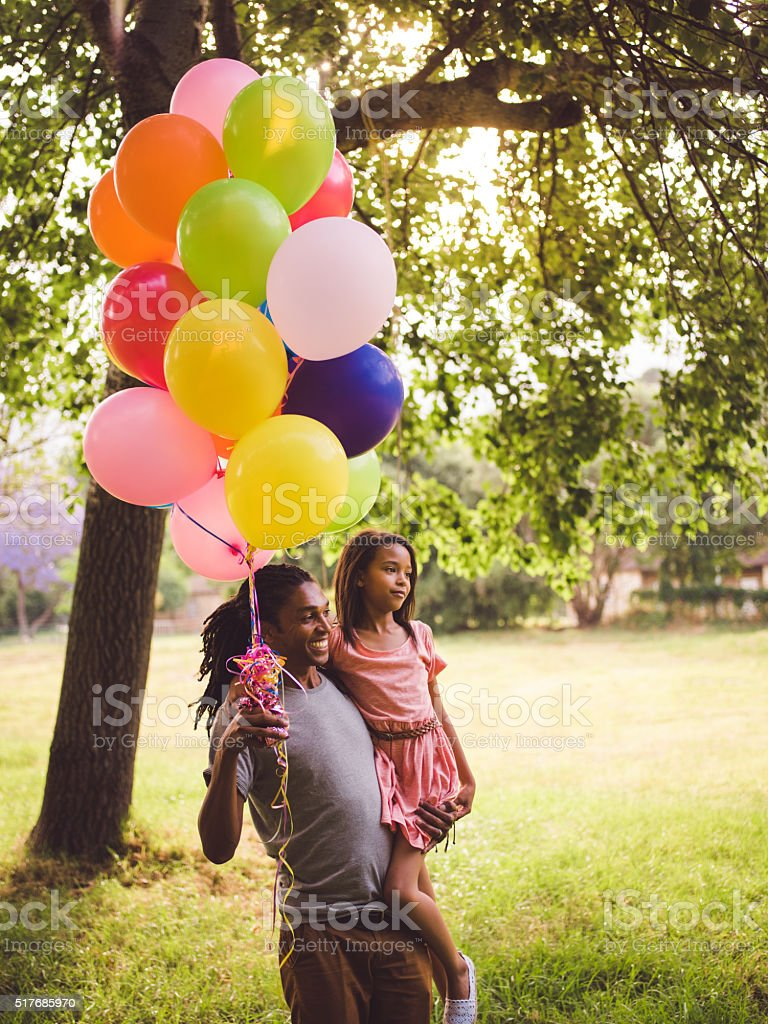 Multi-ethnic father carrying daughter and colourful balloons in stock photo