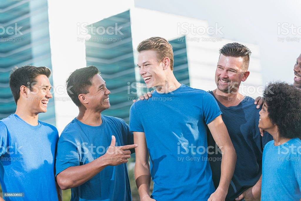 Multi-ethnic fathers and sons wearing blue shirts stock photo