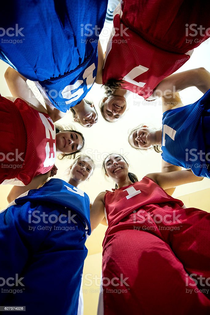 Multi-ethnic female high school basketball team during a huddle stock photo