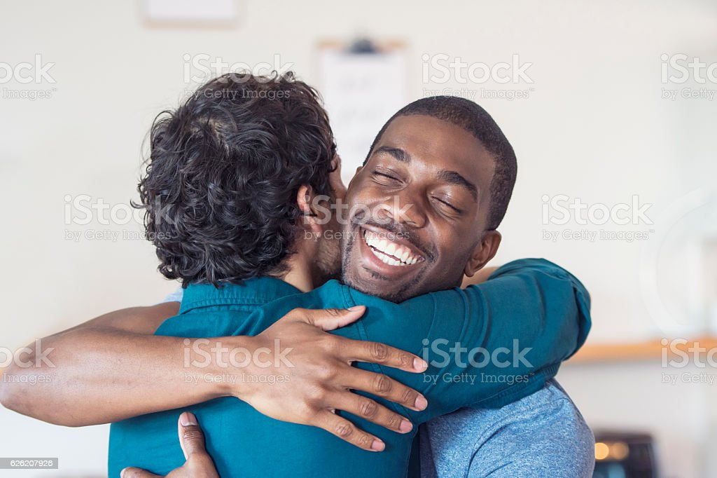 Multi-ethnic gay couple embracing stock photo