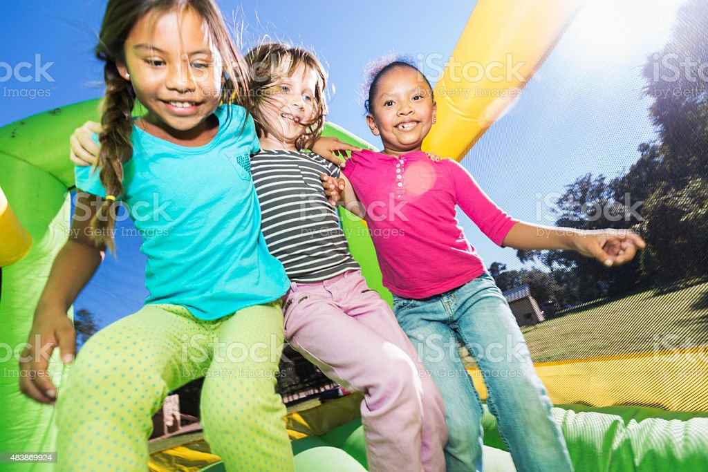 Multi-ethnic girls jumping together on bounce house stock photo