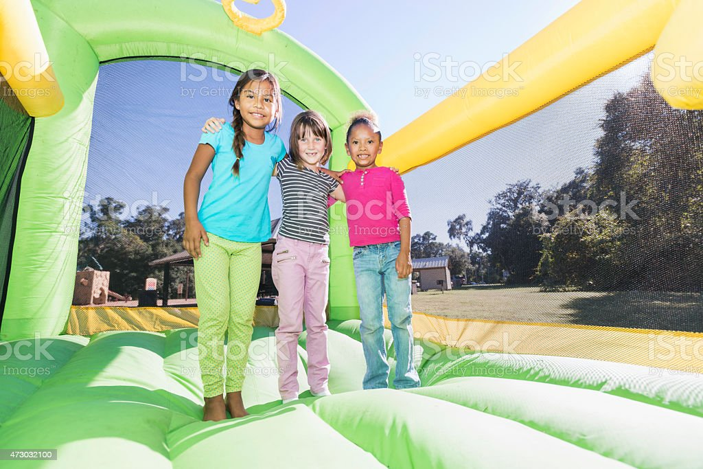 Multi-ethnic girls standing together on bounce house stock photo