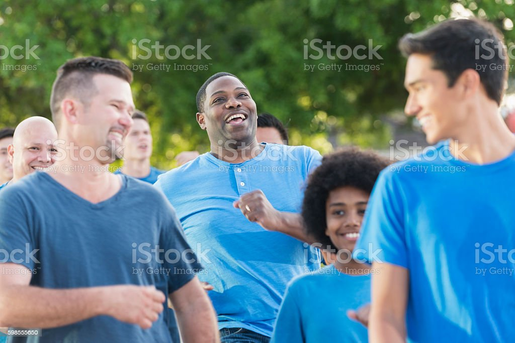 Multi-ethnic gorup of boys and men wearing blue shirts stock photo