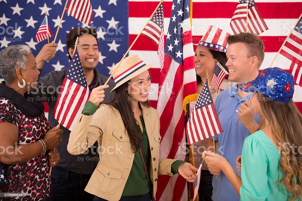 Multi-ethnic group. American people at political rally. USA flags. Voting. stock photo
