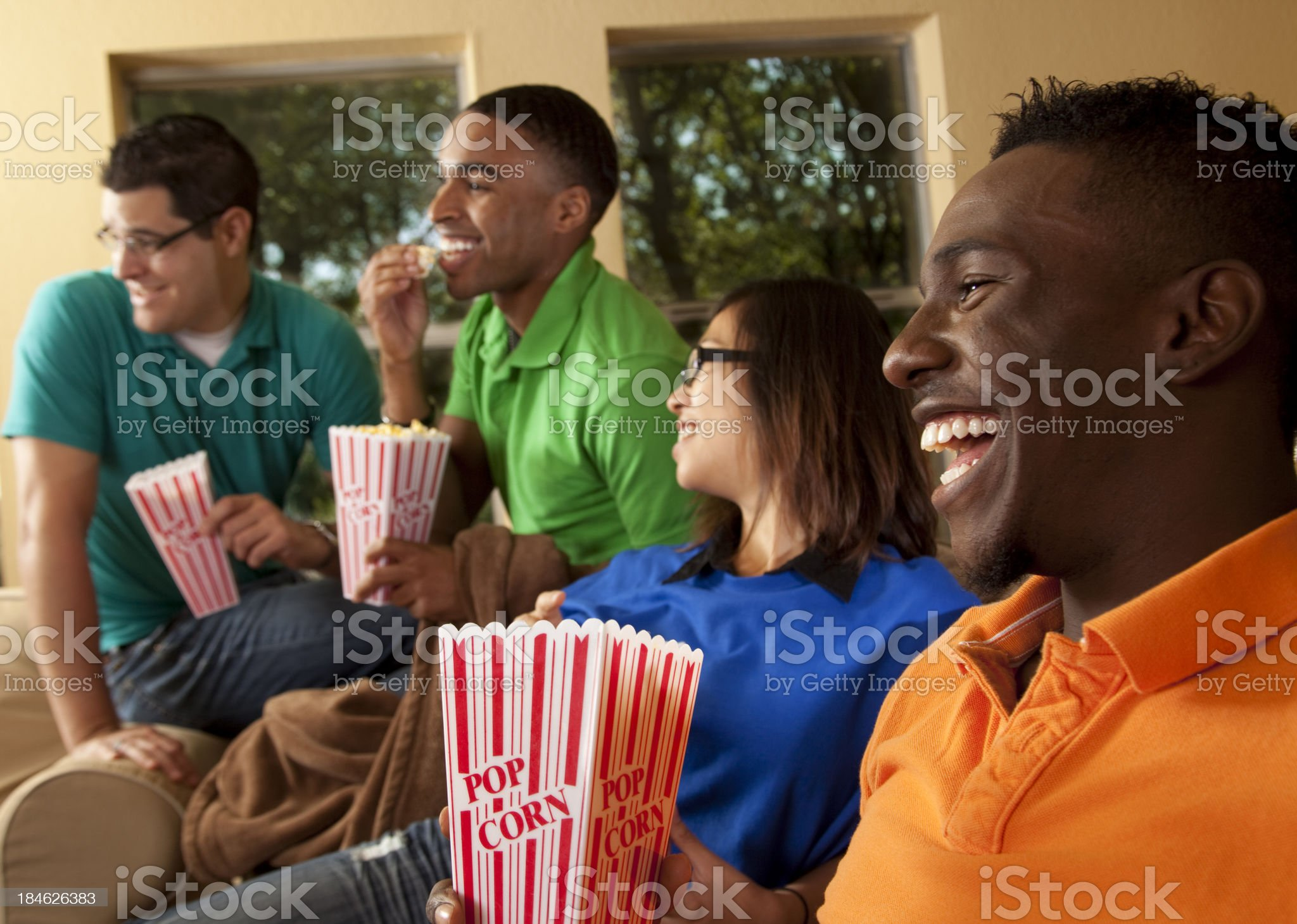 Multi-ethnic group friends eating popcorn as they watch television. Home. royalty-free stock photo