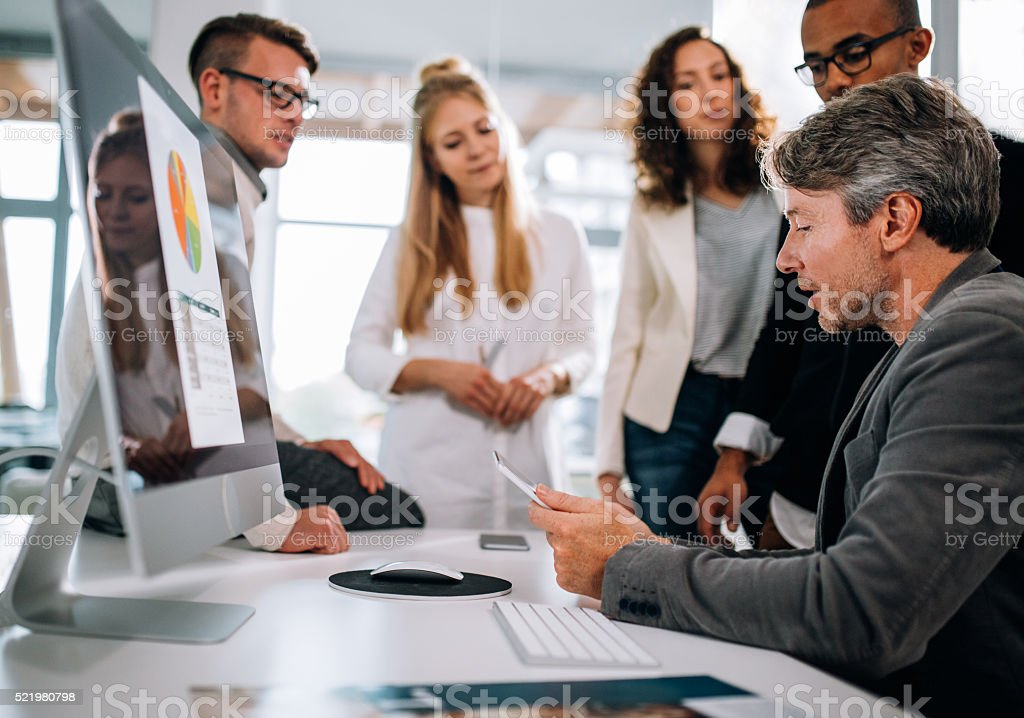 Multi-ethnic group having a quick team meeting at desk stock photo