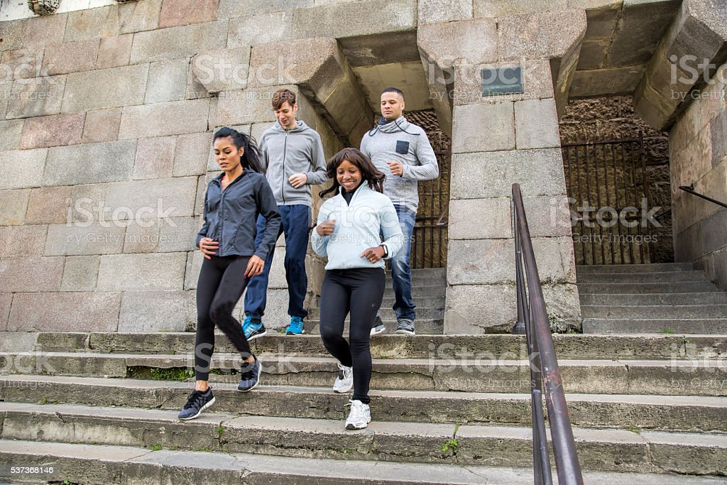 Multi-ethnic group jogging down stairs at Pont Neuf, Paris stock photo