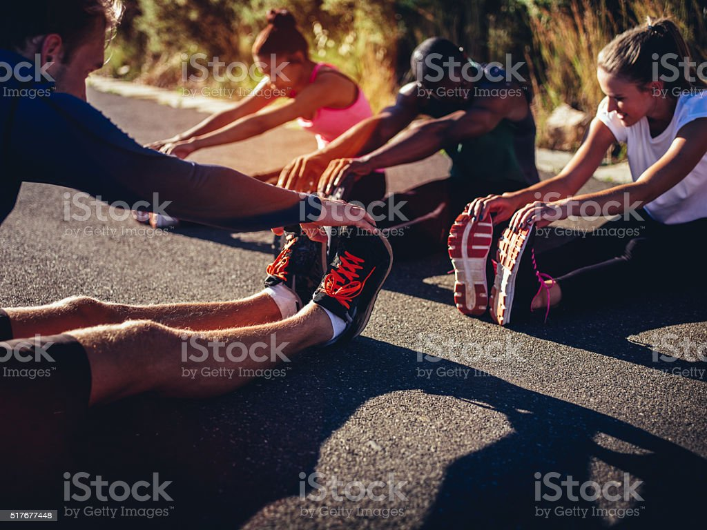 Multi-ethnic group of athletes doing hamstring stretch exercise outside stock photo