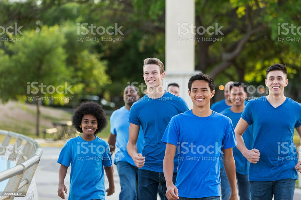 Multi-ethnic group of boys and men wearing blue shirts stock photo
