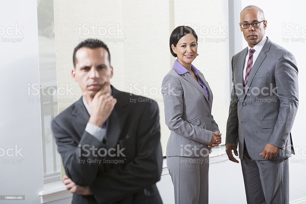 Multi-ethnic group of businesspeople standing in office corridor royalty-free stock photo