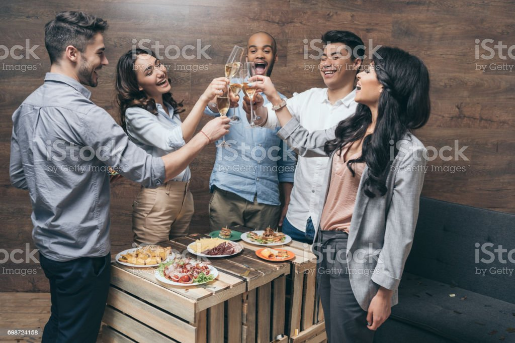 Multiethnic group of cheerful young people clinking champagne glasses above festive table stock photo