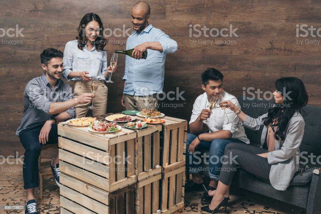 Multiethnic group of cheerful young people talking and drinking champagne indoors stock photo