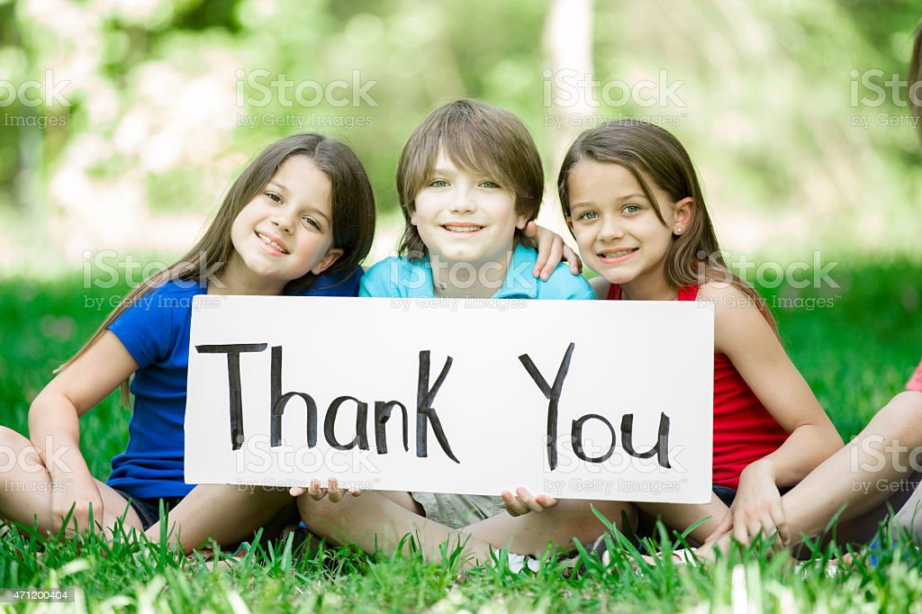 Multi-ethnic group of children hold 'Thank You' sign outdoors. Summer. stock photo