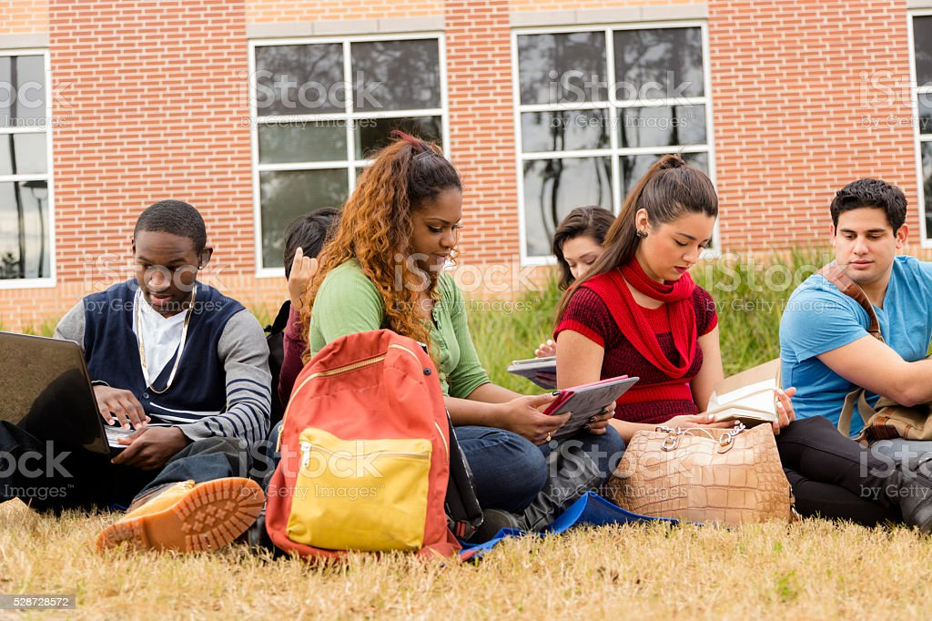 Multi-ethnic group of college student friends. Digital tablet, laptop. stock photo