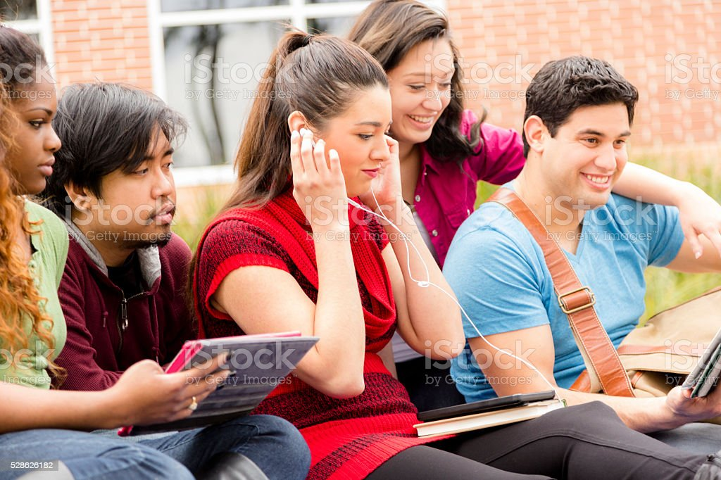 Multi-ethnic group of college student friends. Digital tablets. stock photo