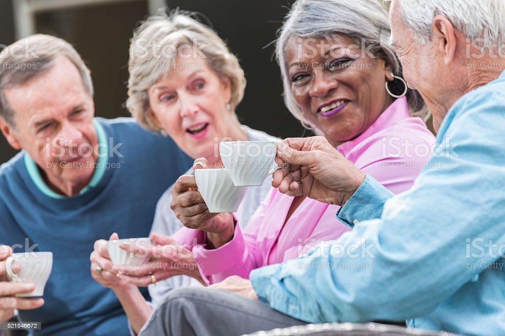 Multi-ethnic group of four seniors sitting outdoors stock photo