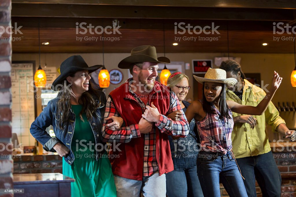 Multi-ethnic group of friends dancing in a bar stock photo