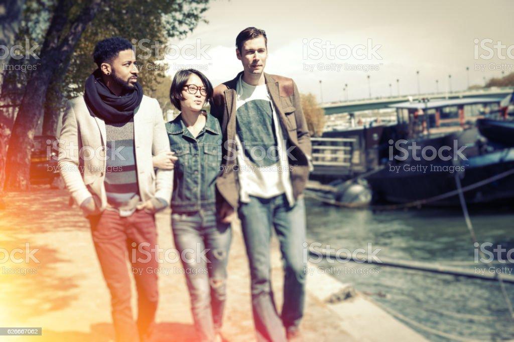 Multi-ethnic group of friends having fun in Paris along Seine stock photo