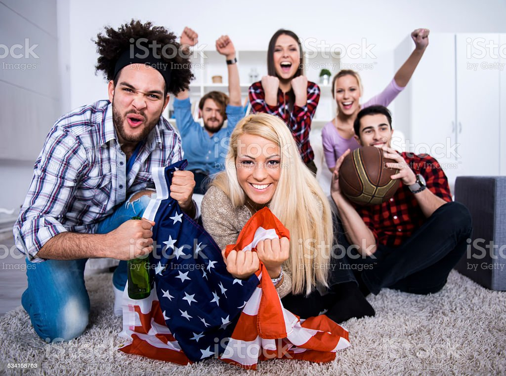 Multiethnic group of friends watching a basketball game stock photo