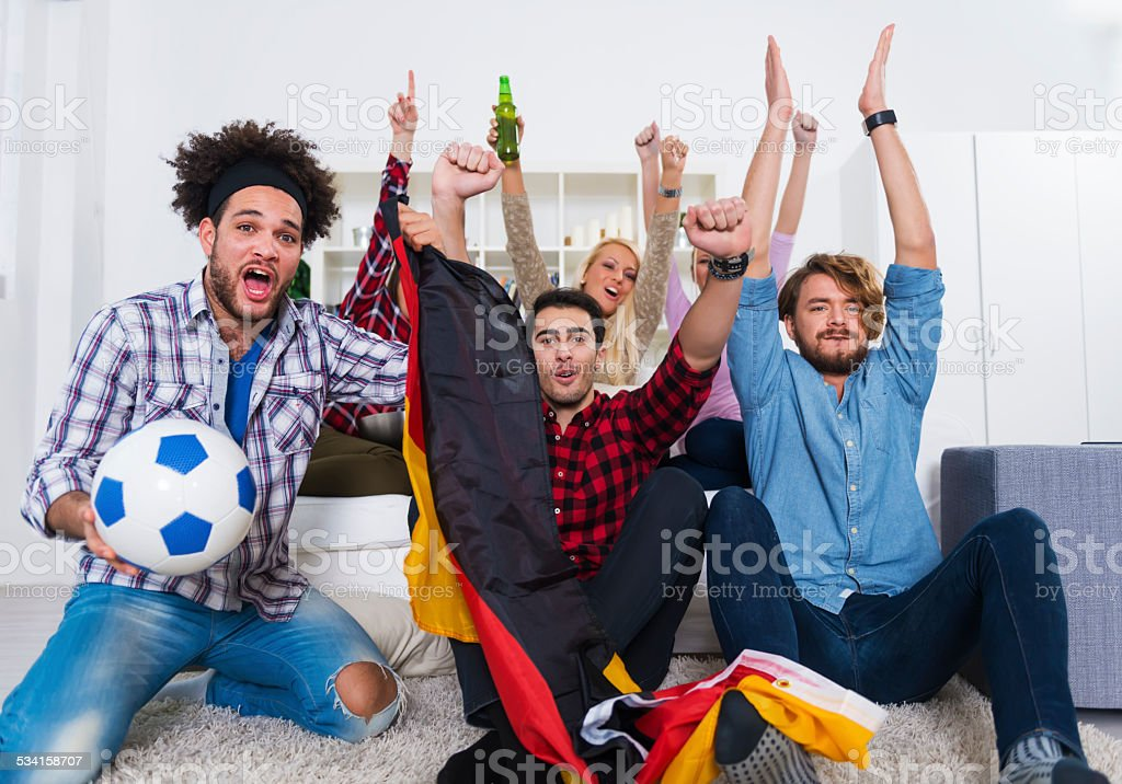 Multiethnic group of friends watching a football game stock photo