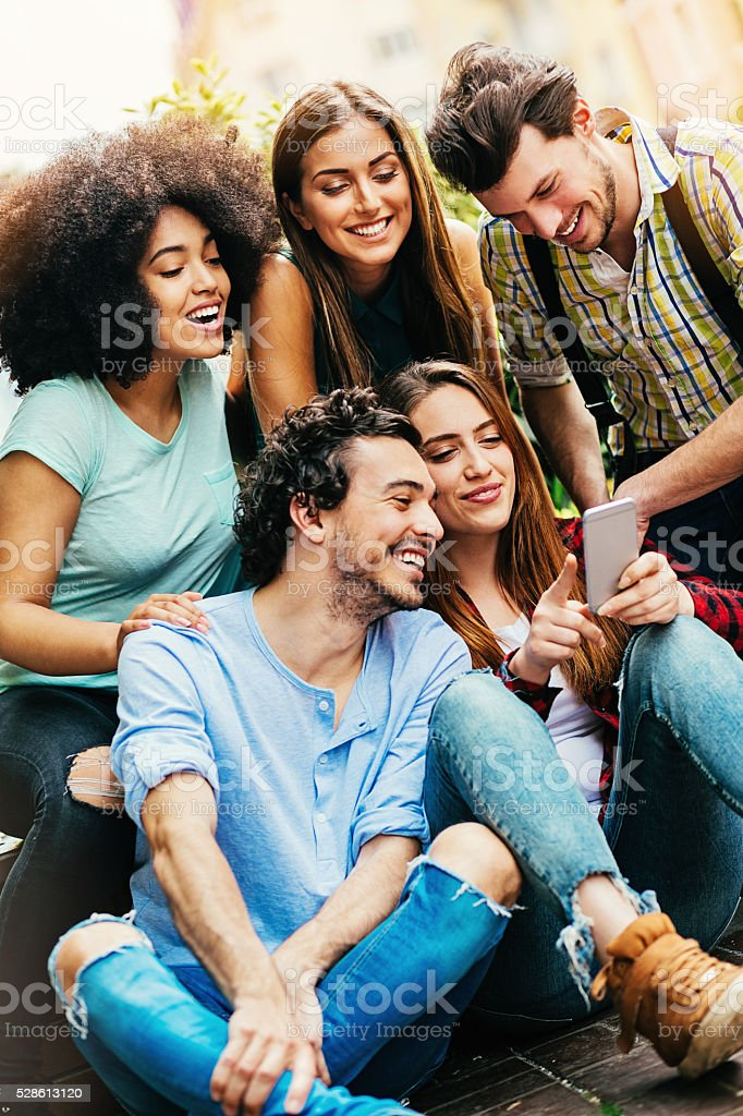 Multi-ethnic group of friends with a phone stock photo