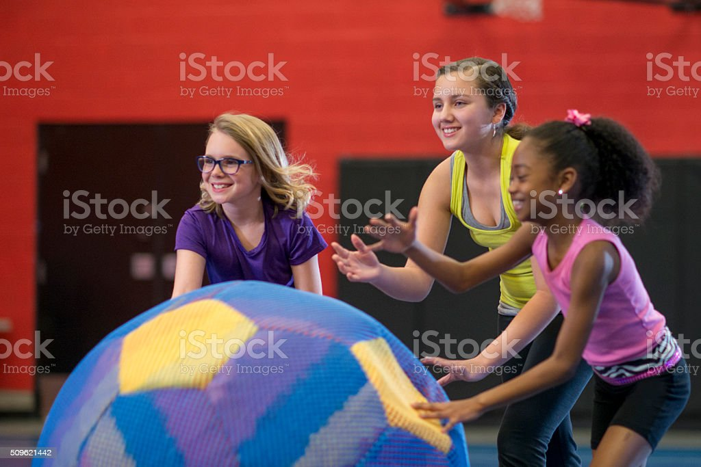 A multi-ethnic group of girls are rolling a large stock photo