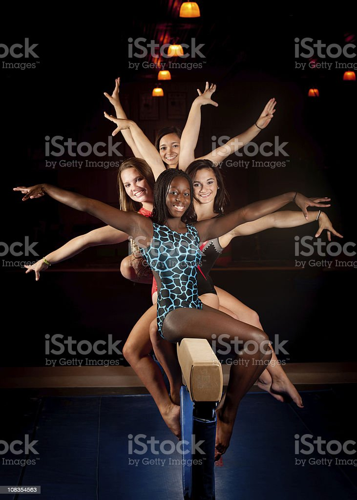 Multi-ethnic group of gymnasts in fun pose on balance beam stock photo