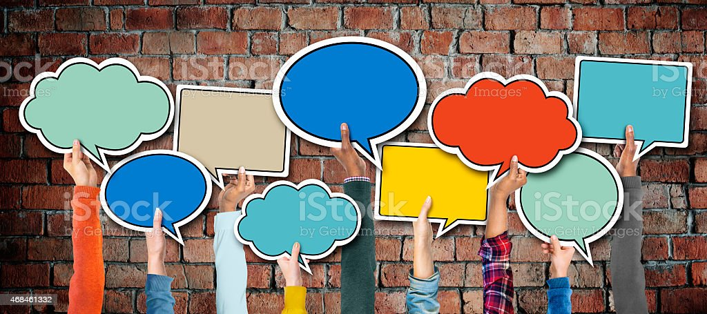 Multi-Ethnic Group of Hands Holding Speech Bubbles stock photo