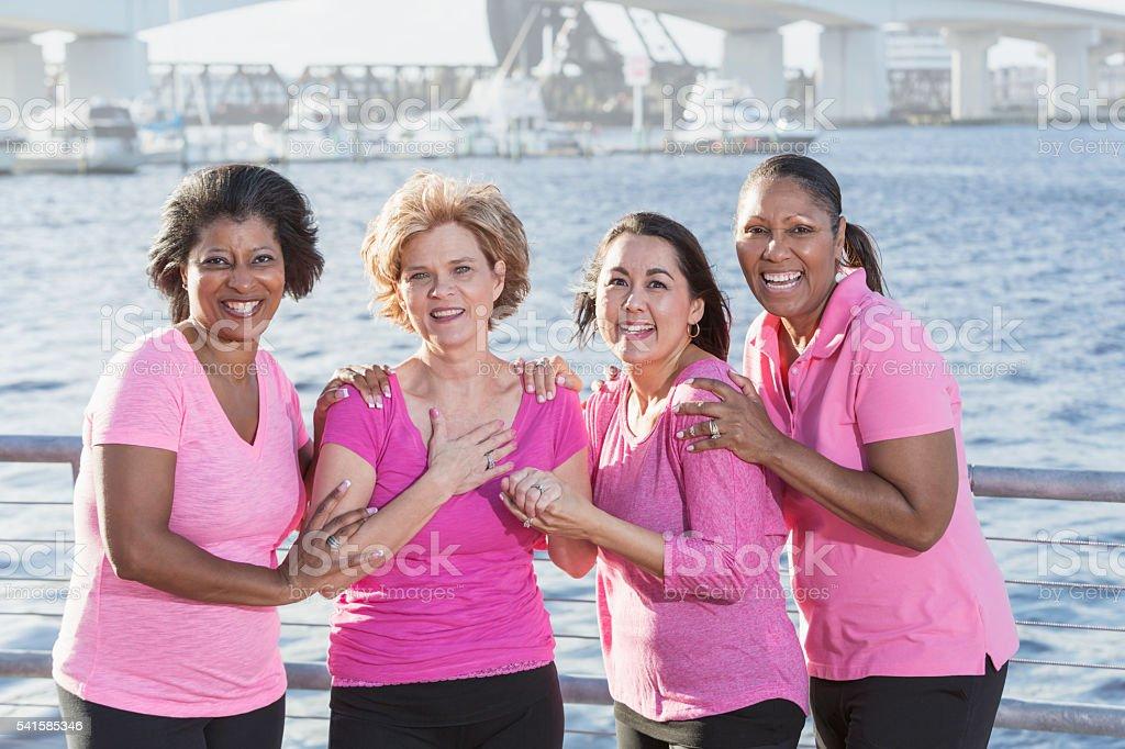 Multi-ethnic group of mature women wearing pink shirts stock photo