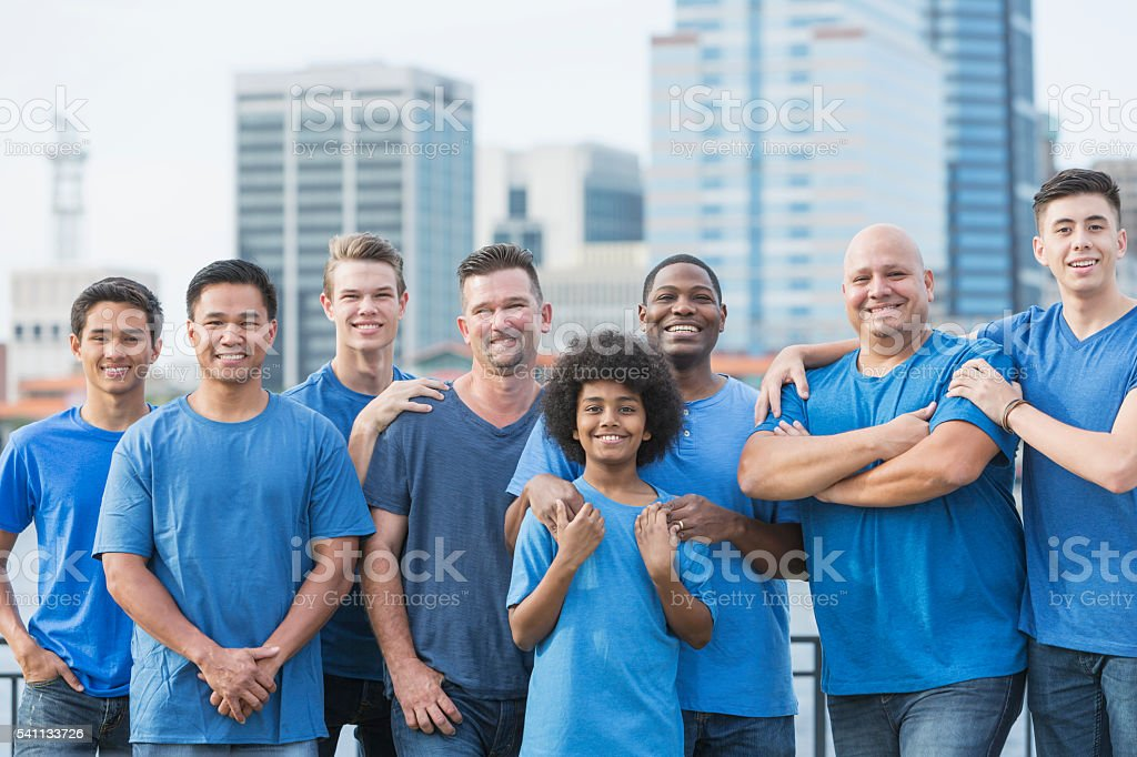 Multi-ethnic group of men and sons volunteering stock photo