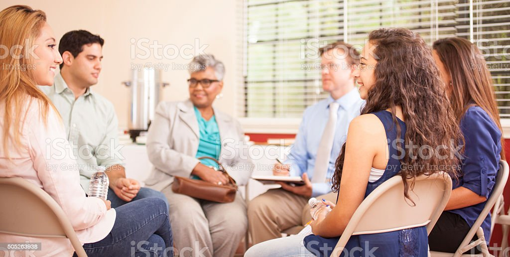 Multi-ethnic group of people in counseling session with therapist. stock photo