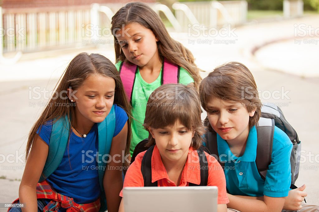 Multi-ethnic group of school children enjoy digital tablet. stock photo