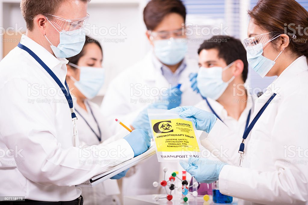 Multi-ethnic group of scientists in science laboratory. Cancer research. stock photo