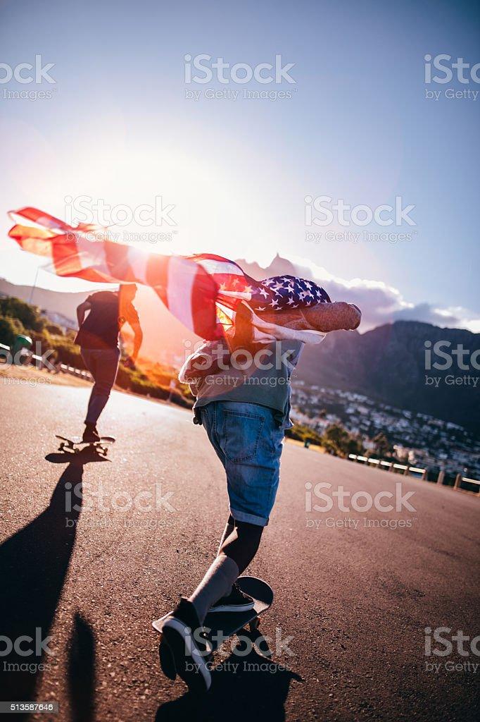 Multi-Ethnic Group of Skaters Skateboarding Down Street at Seasi stock photo