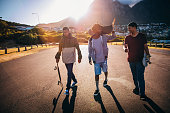 Multi-Ethnic Group of Skaters Walking Down Street at Seaside