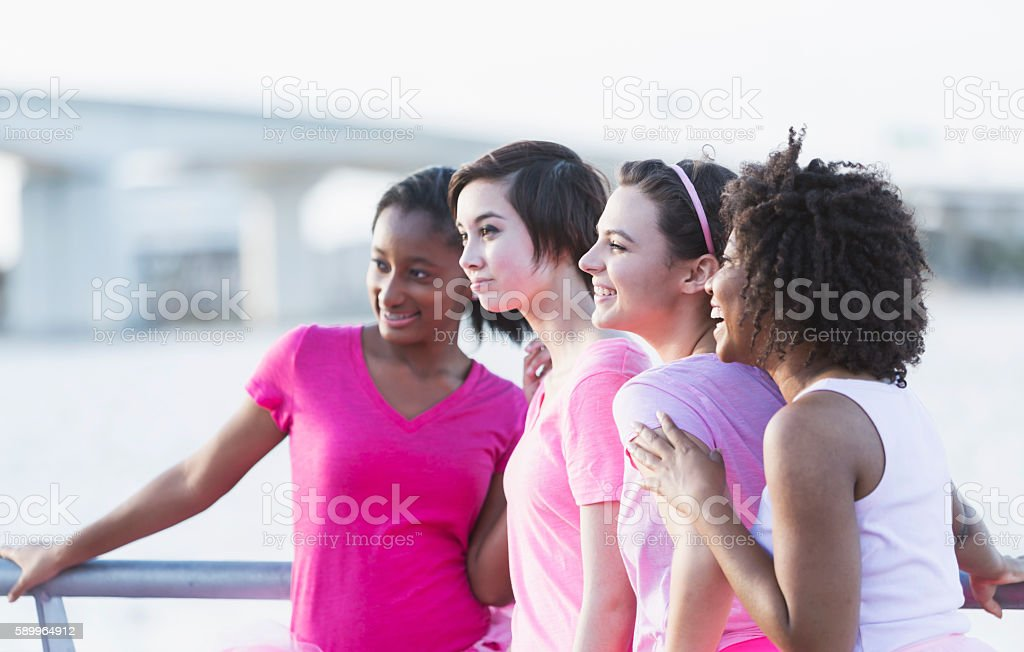 Multi-ethnic group of teenagers and young women in pink stock photo
