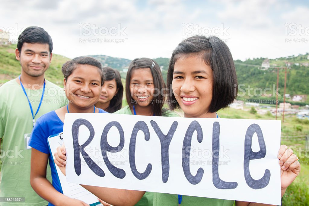Multi-ethnic group of teenagers hold 'recycle' sign outdoors. stock photo