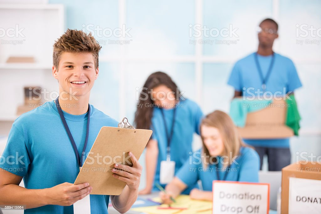 Multi-ethnic group of teenagers organize local donation event. stock photo