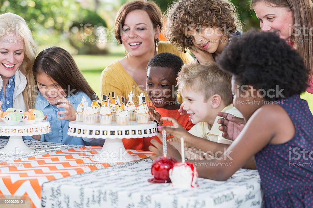 Multi-ethnic group of women and children at fall party stock photo