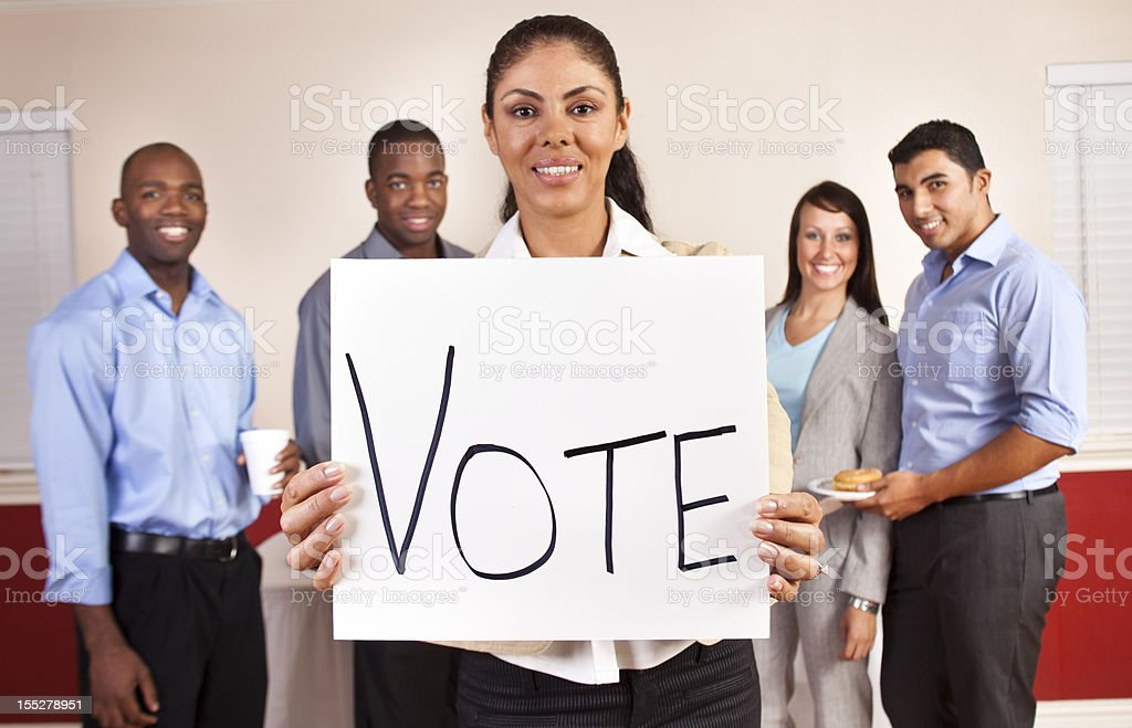 Multi-ethnic group of young adult business people with Vote sign. royalty-free stock photo