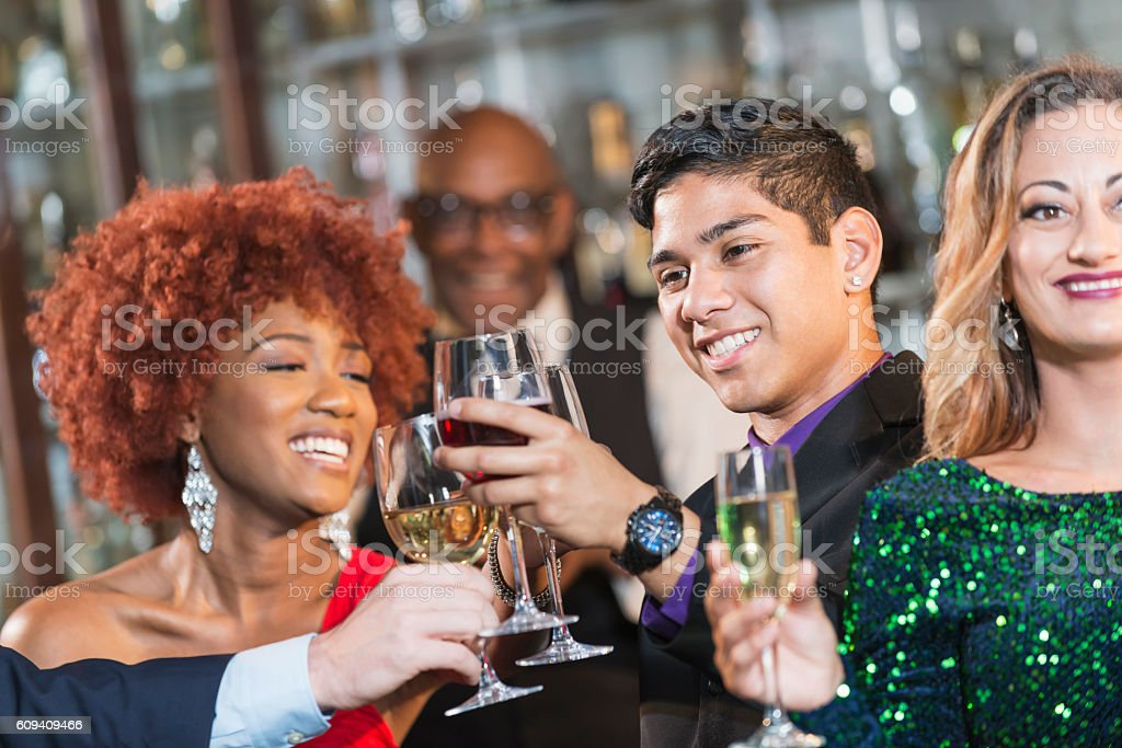 Multi-ethnic group of young adults at a bar drinking stock photo