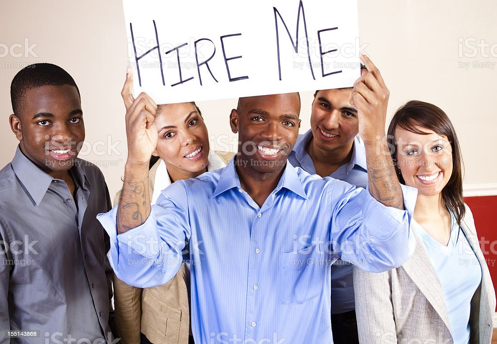 Multi-ethnic group of young adults. Business people. 'Hire Me' Sign. royalty-free stock photo