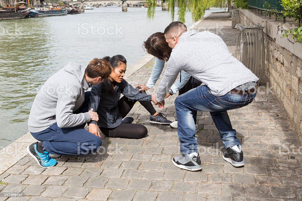 Multi-ethnic group of young joggers helping a woman stock photo