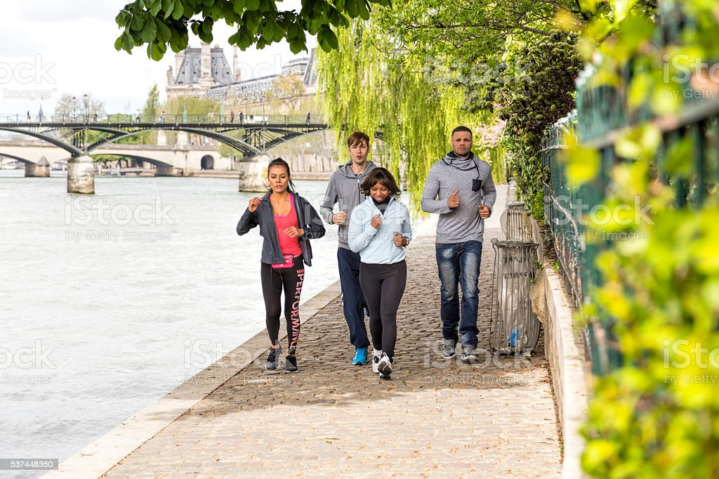 Multi-ethnic group of young people jogging by the Seine, Paris stock photo