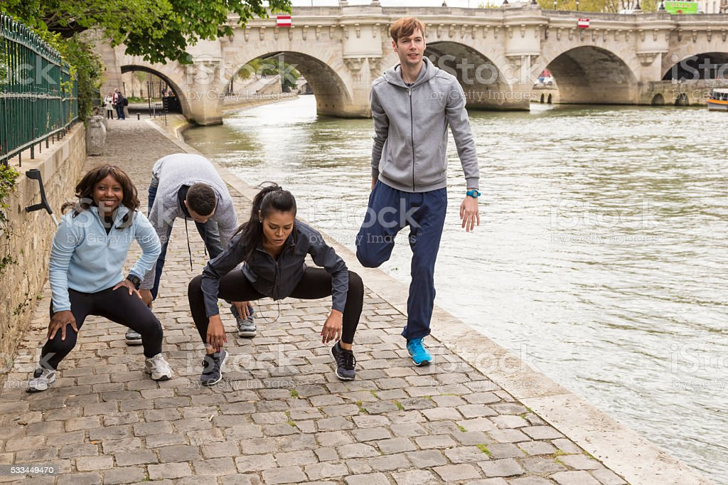 Multi-ethnic group of young people streching after jogging, Paris stock photo