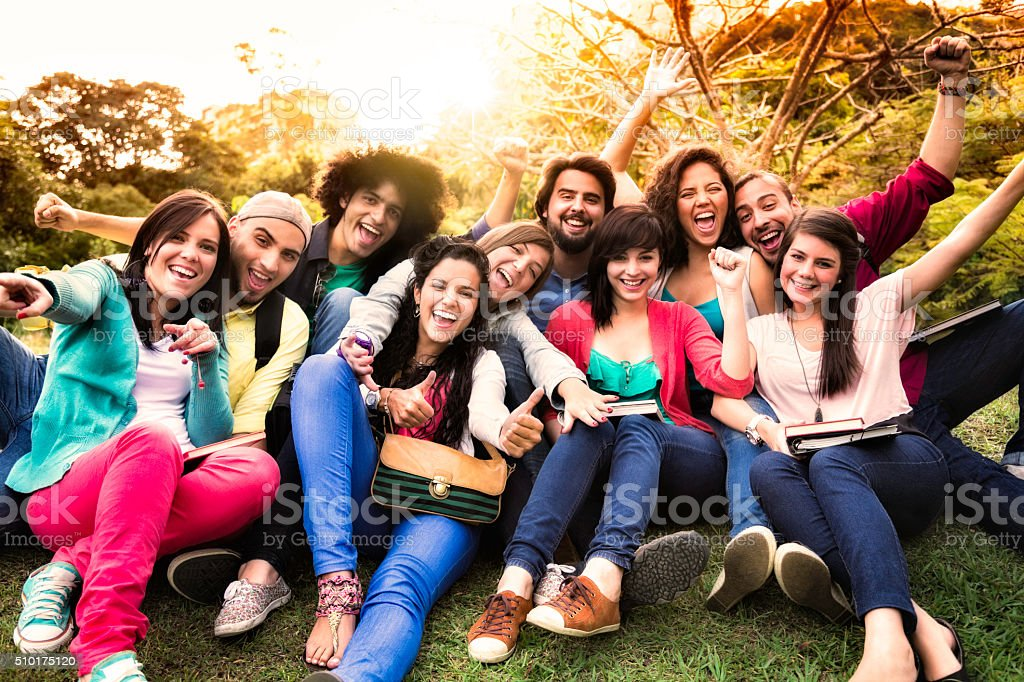 Multi-ethnic group of young students having fun at university campus stock photo