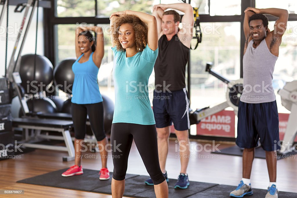 Multi-ethnic group stretching in a gym stock photo